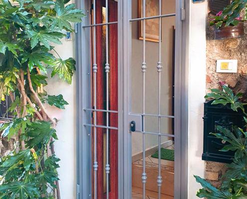 Inferriata in ferro porta doppia anta con barra decorata colore grigio